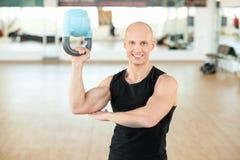 Молодой мышечный человек делая тренировку с kettlebell Стоковая Фотография