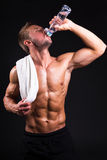 Молодой мышечный человек после тренировки питьевой воды от бутылки Стоковые Фотографии RF