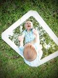 Молодой младенец смотря собственную личность в зеркале пока усмехающся стоковое изображение rf