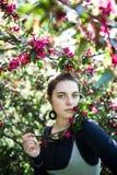 Молодой наслаждаться девочка-подростка blossoming дерева цветет запах в солнечном парке Красота весеннего времени без аллергии Стоковая Фотография