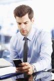 Молодой обмен текстовыми сообщениями бизнесмена на мобильном телефоне Стоковое фото RF
