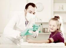 Молодой доктор готовый для того чтобы сделать впрыску к посетителю стоковое изображение