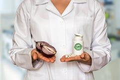 Молодой доктор держа 2 половины лука и бутылки острословия пилюлек Стоковое Фото