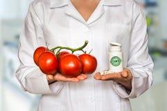Молодой доктор держа томаты и бутылку пилюлек с витаминами Стоковая Фотография