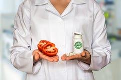 Молодой доктор держа томат и бутылку пилюлек с витаминами Стоковое фото RF