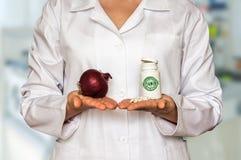 Молодой доктор держа лук и бутылку пилюлек с витаминами и Стоковые Фотографии RF
