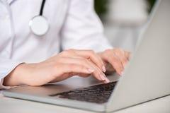 Молодой доктор используя компьтер-книжку в профессиональной клинике Стоковые Фото