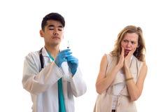 Молодой доктор подготавливая для впрыски молодой женщины Стоковые Фото
