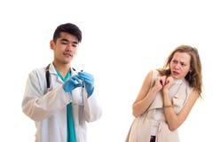 Молодой доктор подготавливая для впрыски молодой женщины Стоковое Фото