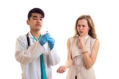 Молодой доктор подготавливая для впрыски молодой женщины Стоковая Фотография RF