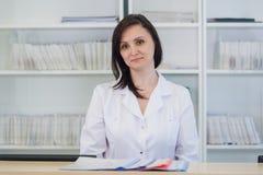 Молодой доктор практикующий врача работая на приемной клиники, она отвечает назначениям телефонных звонков и планировать Стоковые Изображения