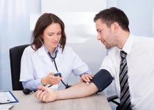 Молодой доктор проверяя кровяное давление стоковое изображение