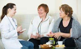Молодой доктор советуя с старшими petients в отечественном интерьере Стоковое Изображение
