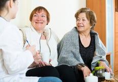 Молодой доктор советуя с старшими petients в отечественном интерьере Стоковая Фотография RF