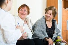 Молодой доктор советуя с старшими petients в отечественном интерьере Стоковое Изображение RF