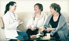 Молодой доктор советуя с старшими petients в отечественном интерьере Стоковые Фотографии RF