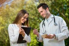 Молодой доктор с детенышами и милый ассистент стоковое изображение