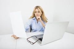 Молодой документ чтения коммерсантки в офисе Стоковое Фото