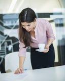 Молодой документ чтения коммерсантки пока держащ кофе в офисе Стоковые Изображения