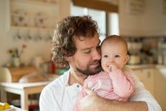 Молодой отец держа его маленькую дочь в его подоле стоковое фото rf