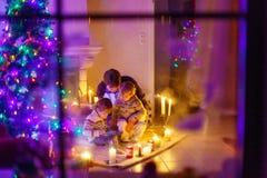 Молодой отец и его маленькие дети сидя камином на c Стоковая Фотография RF