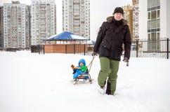 Молодой отец и мальчик наслаждаясь ездой саней Sledding ребенка Розвальни катания ребенк малыша Игра детей outdoors в снеге малыш Стоковая Фотография RF
