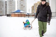 Молодой отец и мальчик наслаждаясь ездой саней Sledding ребенка Розвальни катания ребенк малыша Игра детей outdoors в снеге малыш Стоковая Фотография