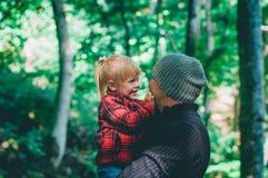 Молодой отец при его маленькая дочь имея потеху в лесе стоковое фото