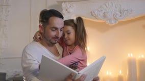 Молодой отец сидя с дочерью на камине и говоря рассказ на Рожденственской ночи сток-видео
