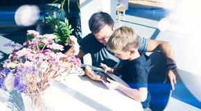 Молодой отец с его 7 летами старого маленького сына играя цифровую таблетку на солнечном доме Концепция счастливой семьи тратя вр Стоковое Изображение