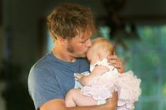 Молодой отец любяще обнимая и целуя дочь младенца стоковое фото rf