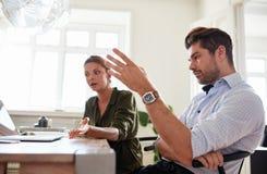 Молодой офис пар дома обсуждая работу Стоковое Изображение