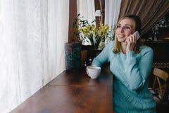 Молодой очаровательный женский фрилансер вызывая с мобильным телефоном пока Стоковая Фотография