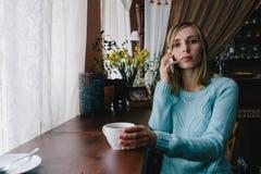 Молодой очаровательный женский фрилансер вызывая с мобильным телефоном пока Стоковое Фото