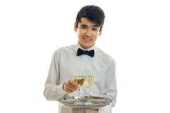 Молодой очаровательный кельнер смотрит прямые улыбки и держит поднос с 2 стеклами вина Стоковые Изображения RF
