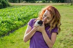Молодой очаровательный фермер женщины с длинными волосами в рубашке, в деревне в его саде идет держащ руки молодого пушистого rab Стоковые Фотографии RF