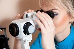 Молодой очаровательный optometrist доктора на работе с прибором для te Стоковая Фотография RF