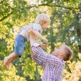 Молодой папа играя с его сыном в парке путем бросать его вверх стоковое фото rf