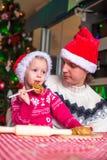 Молодой папа и маленькая дочь в шляпе Санты пекут стоковая фотография