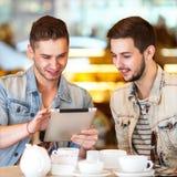 Молодой парень битника сидя в coffe кафа беседуя и выпивая Стоковое Фото