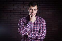 Молодой парень в хмурых взглядах рубашки шотландки Стоковое Изображение