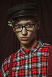 Молодой парень в черной крышке, стеклах и цветках за его ухом Стоковая Фотография