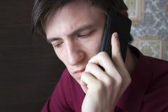 Молодой парень говоря на телефоне, смотря вниз Стоковая Фотография