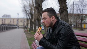 Молодой парень ест горячую сосиску в городе на стенде видеоматериал