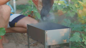 Молодой парень заполняет угли в меднике акции видеоматериалы