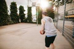 Молодой парень играя баскетбол на внешнем суде Стоковые Фото