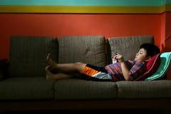 Молодой парень используя таблетку или smartphone на кресле Стоковая Фотография RF
