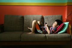 Молодой парень используя таблетку или smartphone на кресле Стоковая Фотография