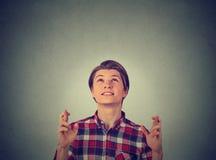 Молодой парень, пальцы скрещивания человека, желая смотреть вверх Стоковые Фотографии RF