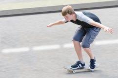 Молодой парень подростка конькобежца в движении двигая дальше скейтборд Стоковое Фото